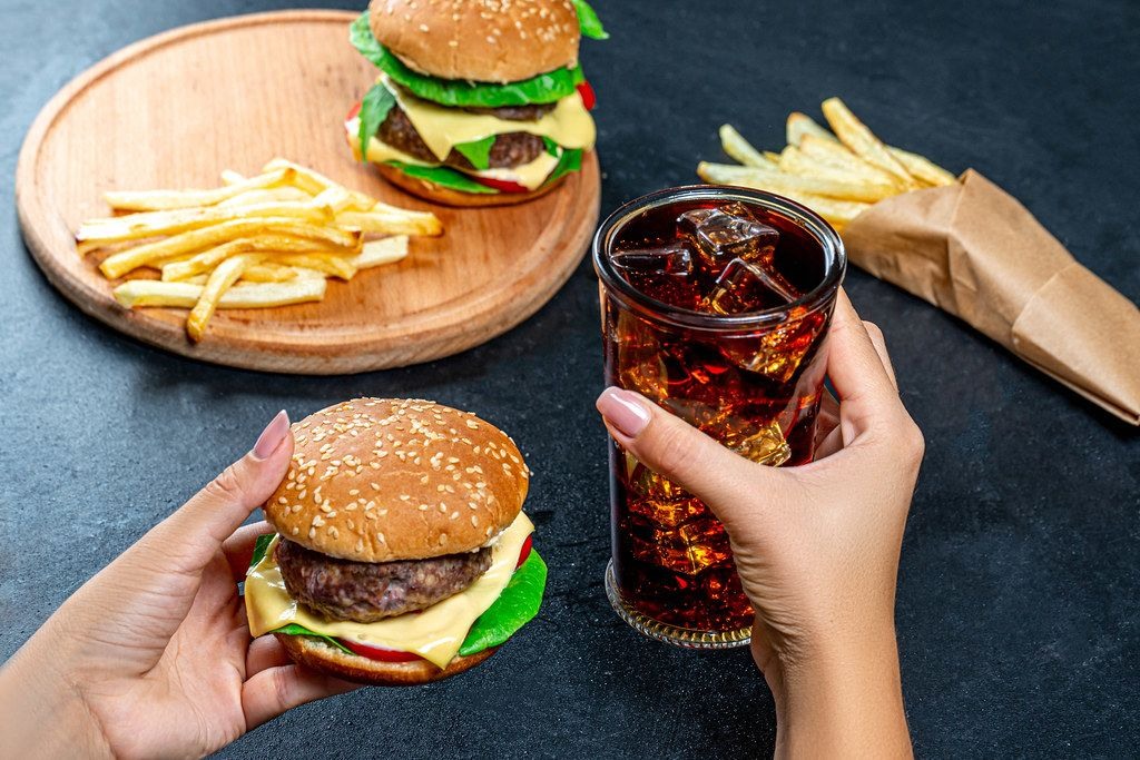 In one hand Burger, in the second the glass with cold Cola. The concept of unhealthy eating