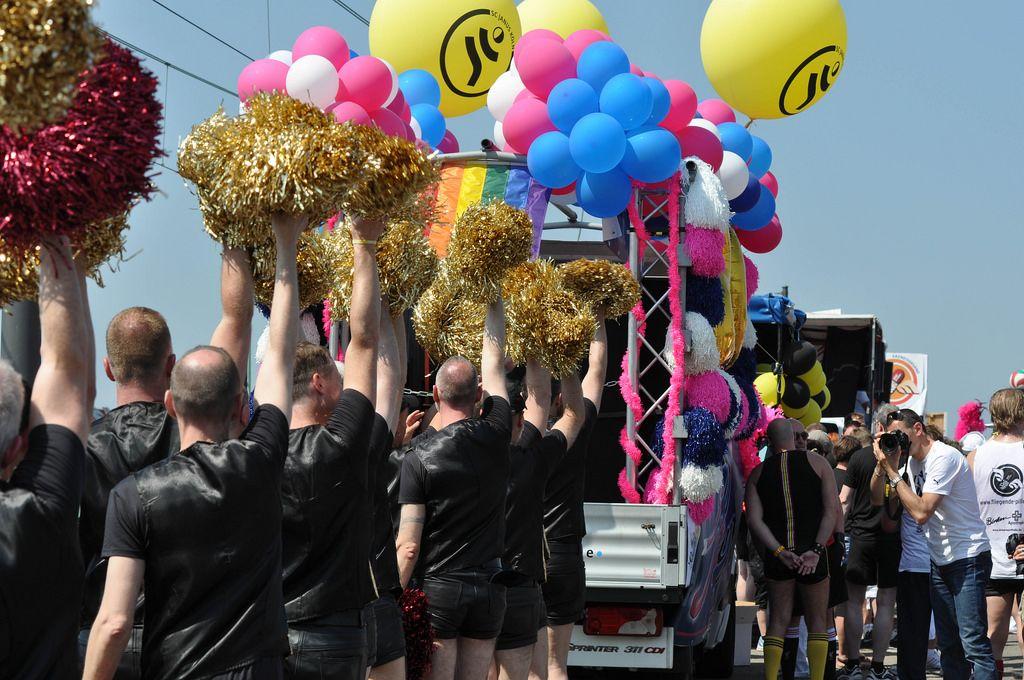 In schwarz gekleidete Männer mit bunten Pompons bei der Cologne Pride Demo