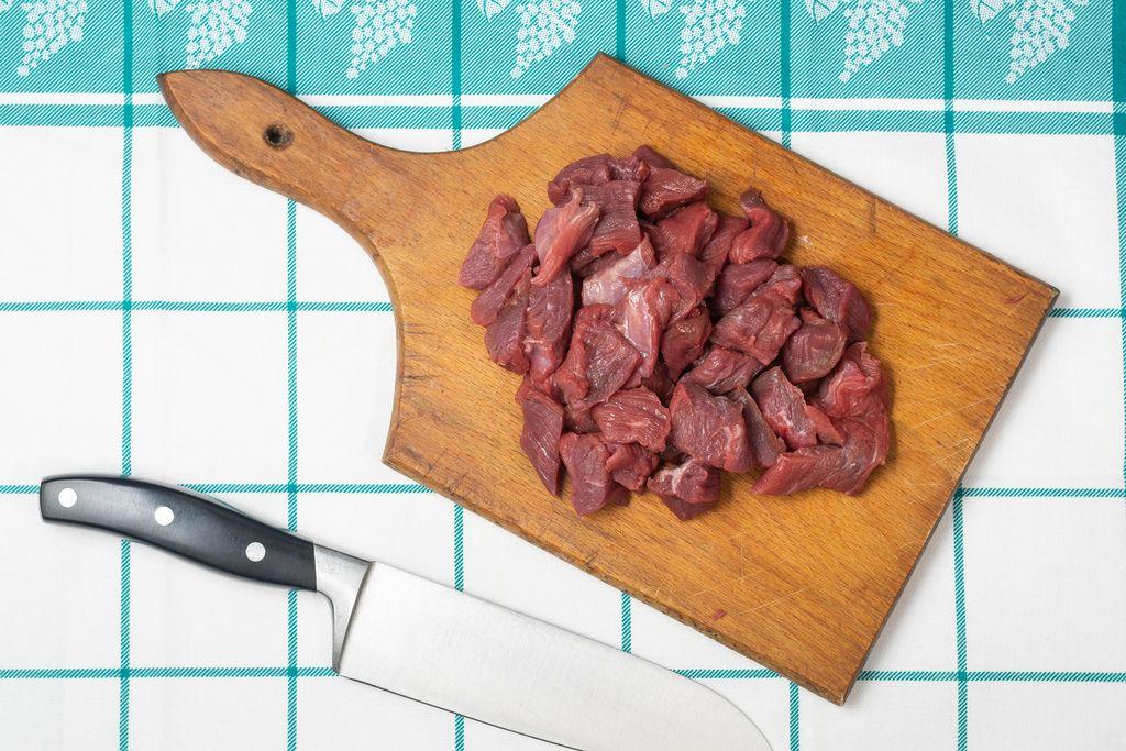 In Stücke geschnittenes rohes Rindfleisch auf Küchenbrett neben Fleischmesser auf Tisch