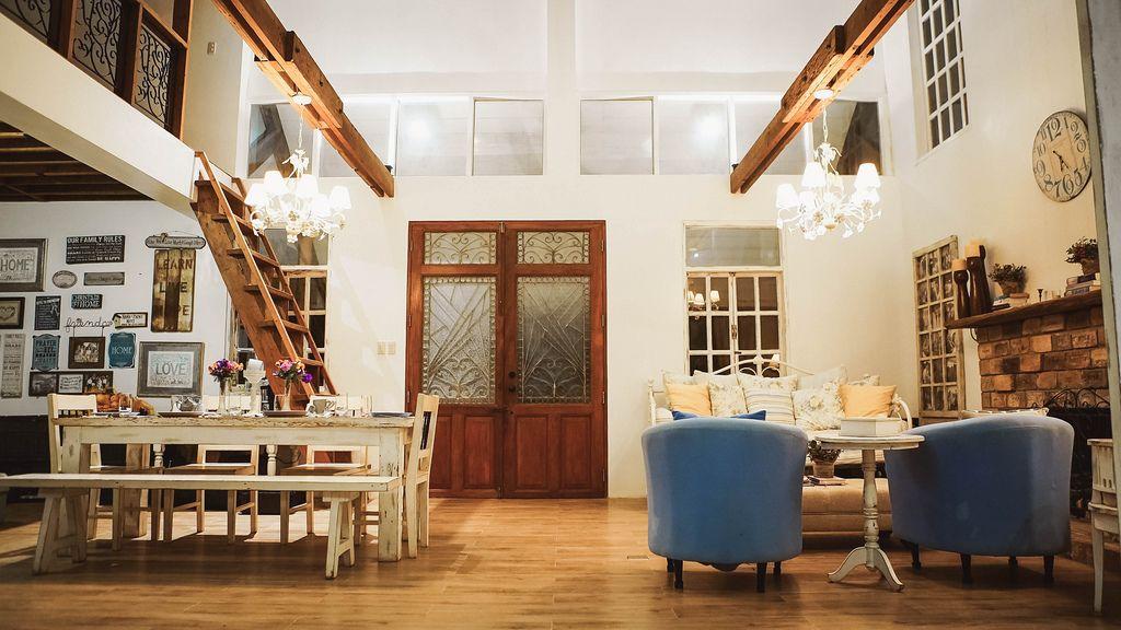 Innenräume eines herrschaftlich eingerichteten Ferienhauses mit Esstisch, Sofa, Sessel und Kamin