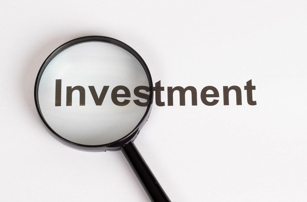 Investment text under magnifying glass