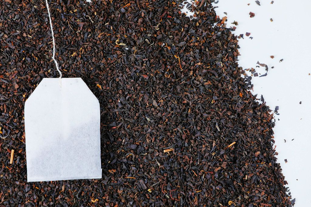 Isolated tea bag on dry tea background