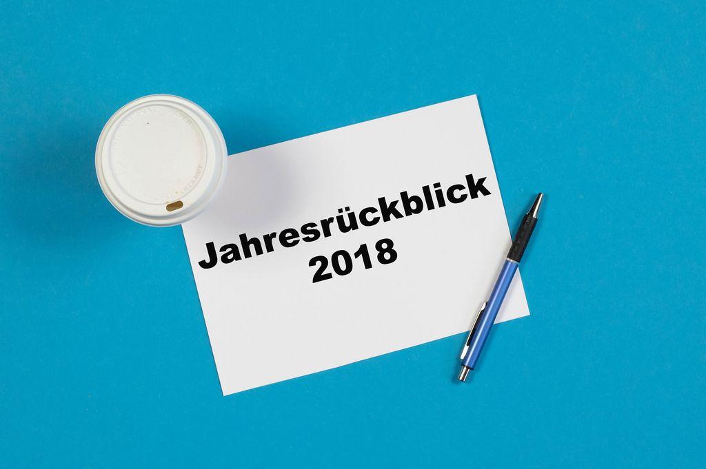 Jahresrückblick 2018 steht auf einem Blatt Papier geschrieben mit Stift und einem Becher Kaffee auf blauem Hintergrund