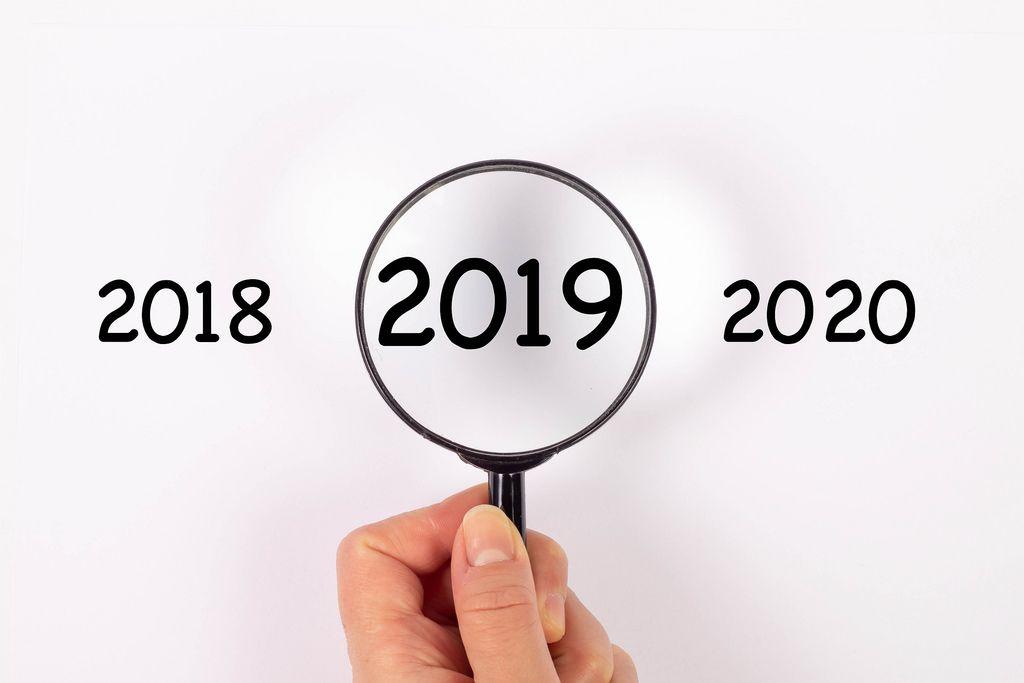 Jahreszahl 2019 unter Lupe, daneben 2018 und 2020 auf weißem Hintergrund