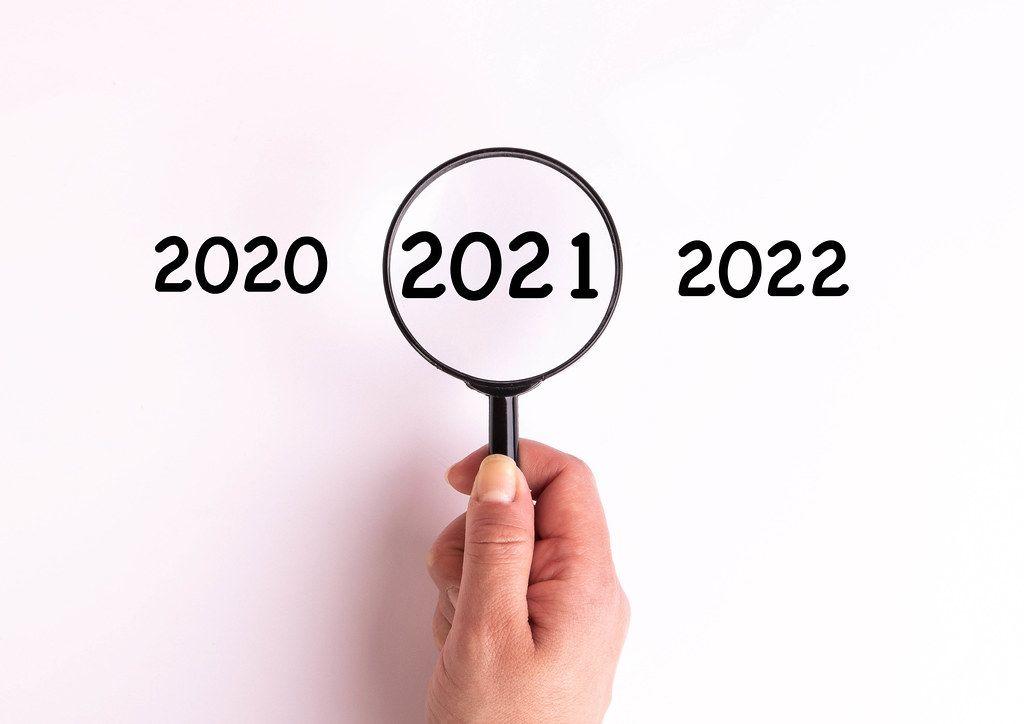 Jahreszahl 2021 auf weißer Oberfläche unter einer Lupe dargestellt