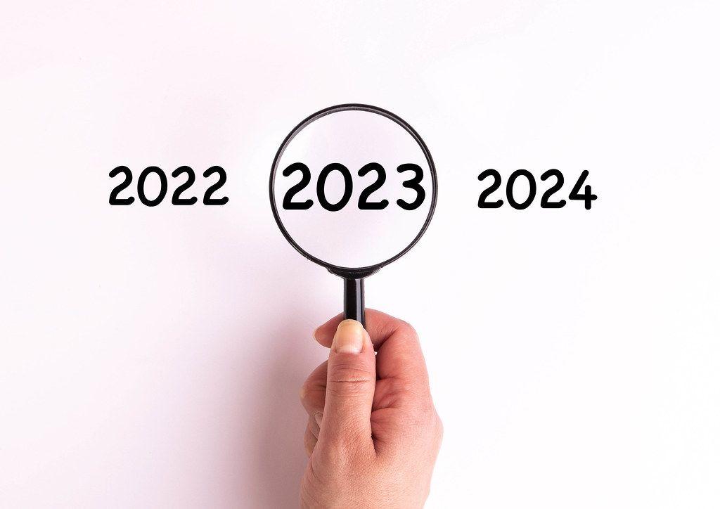 Jahreszahl 2023 auf weißer Oberfläche unter einer Lupe dargestellt