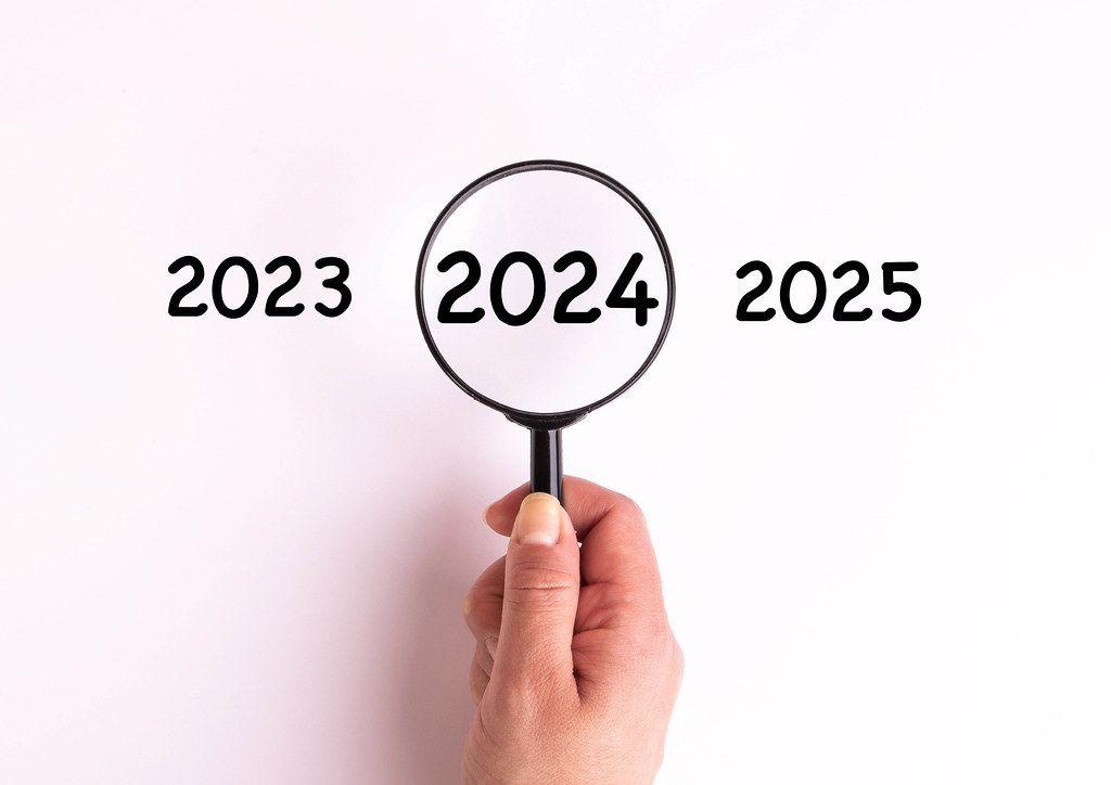 Jahreszahl 2024 auf weißer Oberfläche unter einer Lupe dargestellt