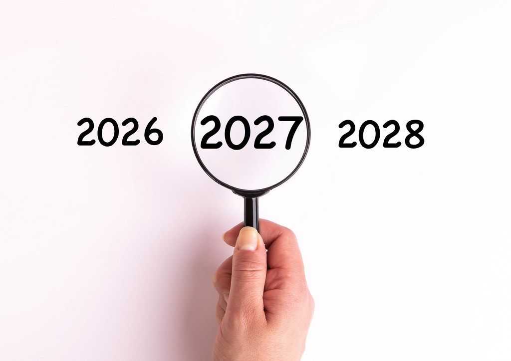 Jahreszahl 2027 auf weißer Oberfläche unter einer Lupe dargestellt