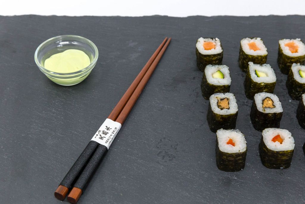 Japanese Chop Sticks with Sushi and Wasabi on black plate
