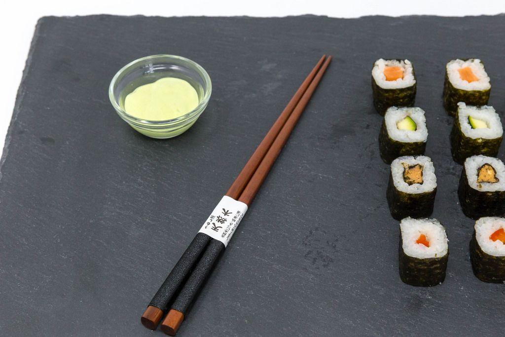 Japanische Essstäbchen mit Sushi und Wasabi auf schwarzer Schieferplatte