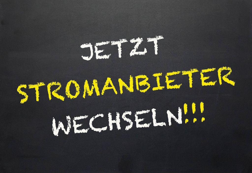 'Jetzt Stromanbieter wechseln!'-Schriftzug mit weißer und gelber Kreide gezeichnet auf Tafel-Untergrund - Nahaufnahme