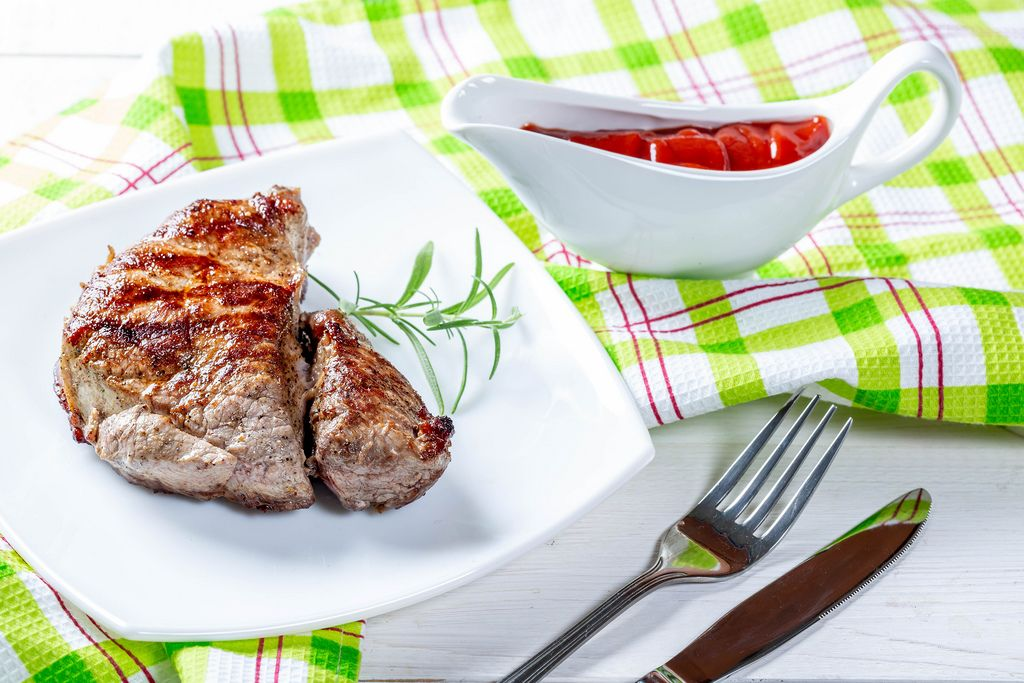 Juicy steak cooked on the grill with tomato sauce