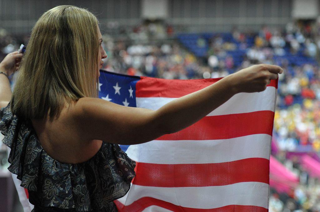 Junge Frau mit US-amerikanischer Flagge in Händen