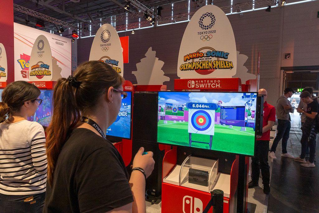 Junge Frau testet das virtuelle Bogenschießen im Videospiel Mario&Sonic bei den Olympischen Spielen, an der Nintendo Switch Spielstation