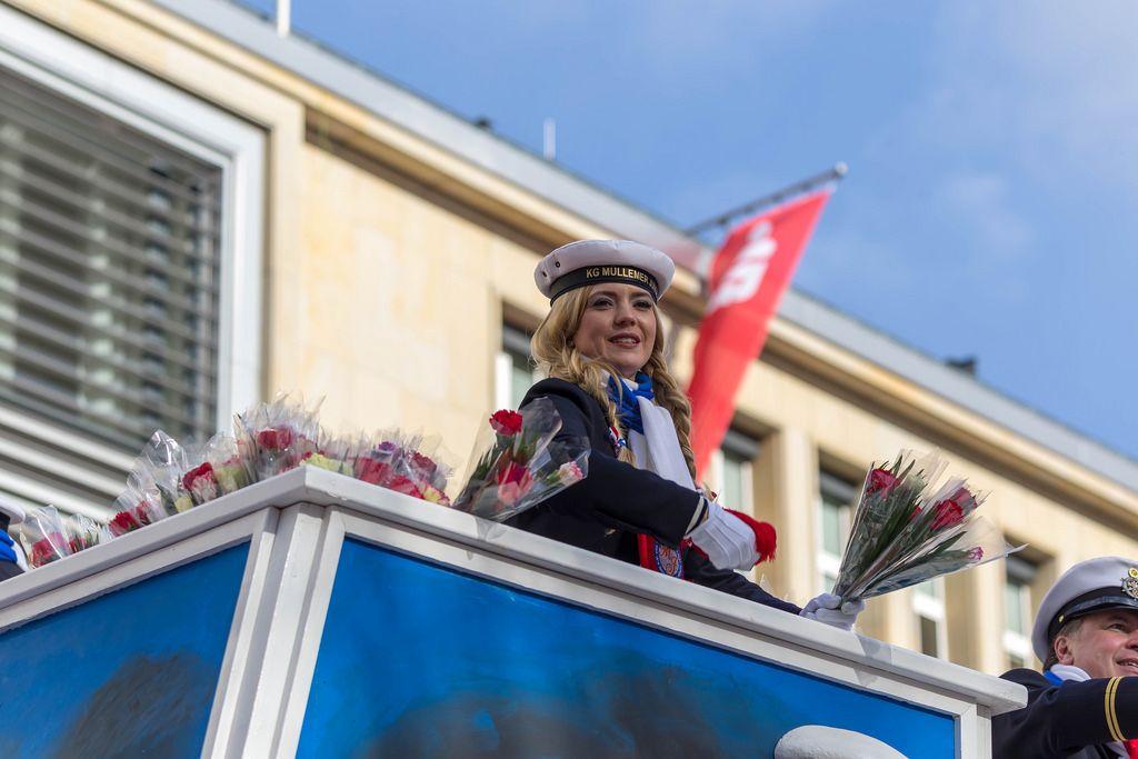 Junge Frau vom Tanzkorps KG Mullemer Junge wirft Publikum Blumen zu - Kölner Karneval 2018