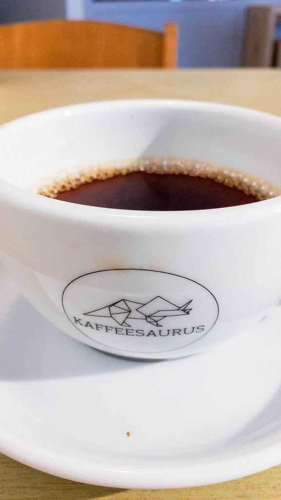 Kaffee in weißer Tasse mit Aufschrift Kaffeesaurus mit Untersetzer auf Holztisch mit Stuhl im Hintergrund
