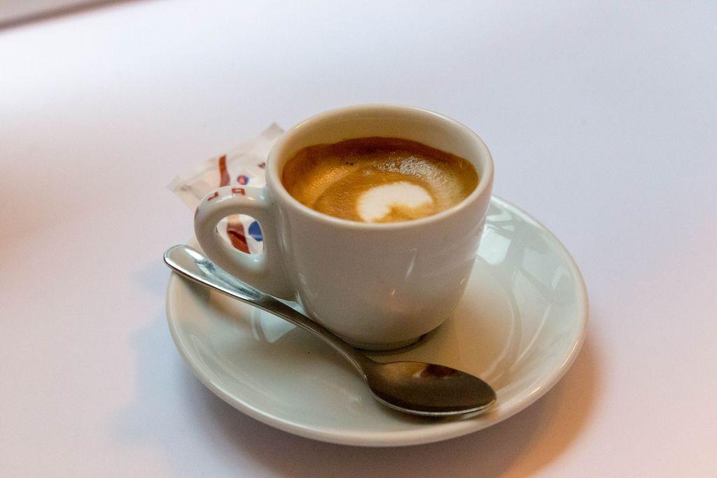 Kaffee mit schöner Crema mit Löffel und Zuckerbeutel auf Untertasse