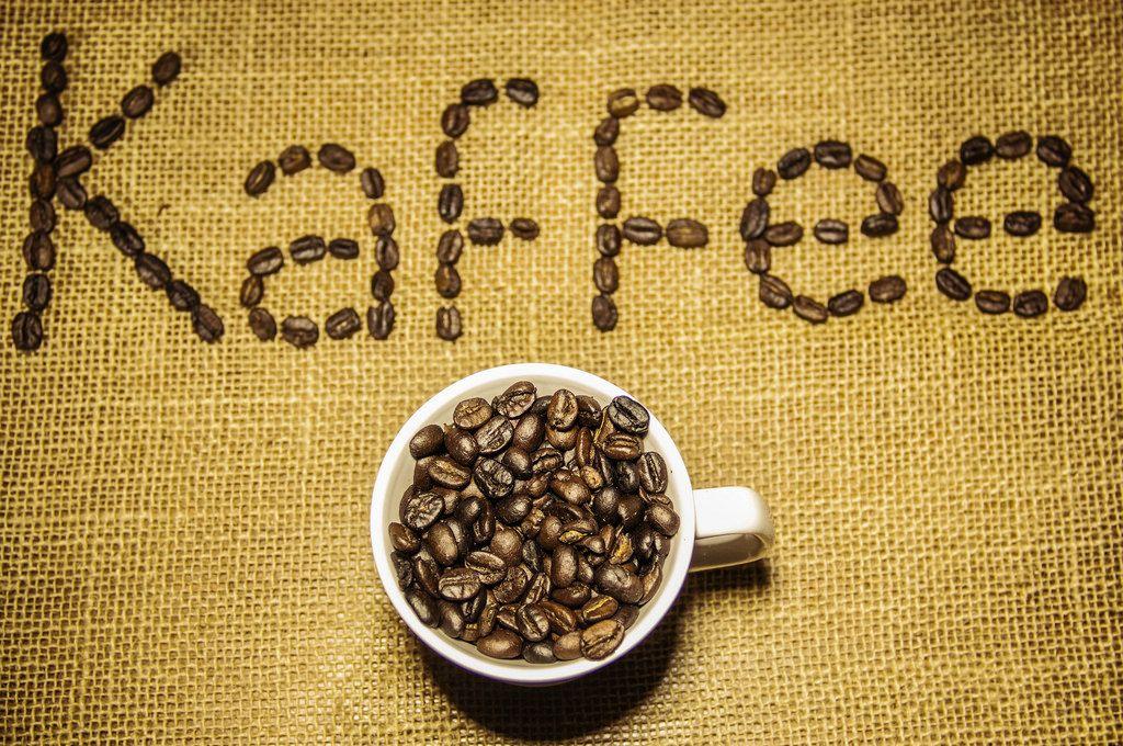Kaffeetasse voll von Kaffeebohnen und Kaffee geschrieben im Hintergrund
