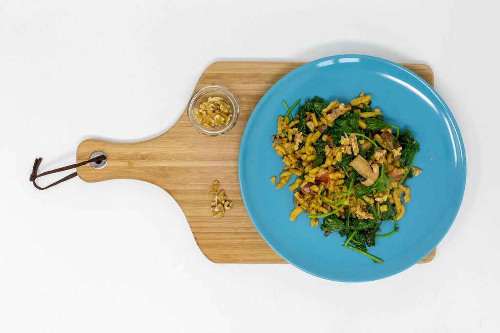 Kale Spätzle Noodles with mushrooms, walnuts and cream sauce on a blue plate, on a wooden chopping board and white background