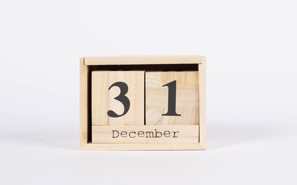 Kalender in Holzkiste zeigt Silvestertag 31. Dezember vor weißem Hintergrund