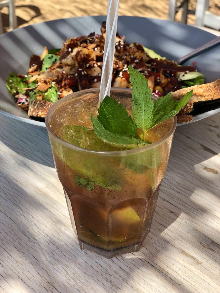 Kaltes Getränk mit Minzblättern & Strohhalm und griechischer Salat mit Hähnchenfleisch, Tomaten, Mais, Zwiebeln, Sesam und Barbecuesauce
