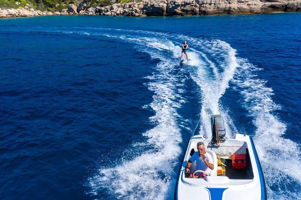 Kapitän im Wasserskiboot zieht einen Wassersportler über das tiefblaue Meer vor dem Felsenstrand von Spetses, Griechenland, als Luftaufnahme