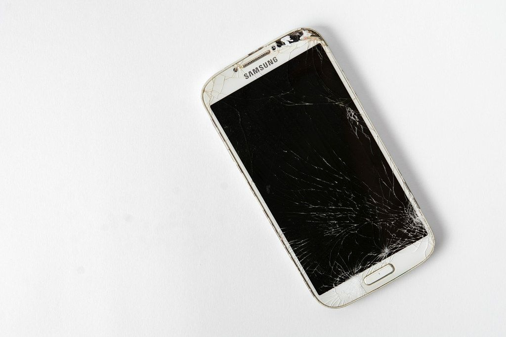 Kaputtes Smartphone mit gesprungenem, zebrochenem Display auf weißem Hintergrund, mit Platz für eigenen Text