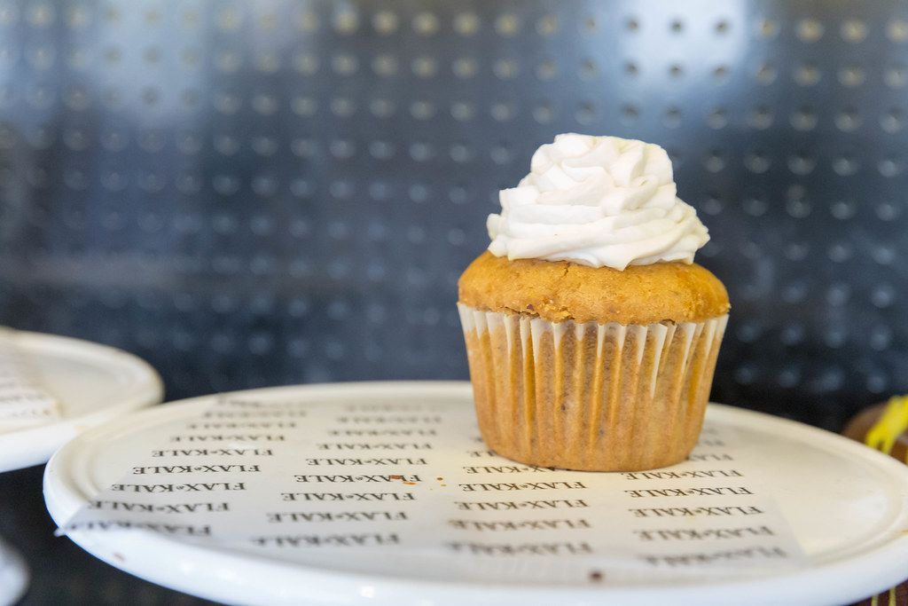 Karotten-Kokosnuss Cupcake aus Vollkornreis und Buchweizenmehl mit Zimt, Apfel, Muskatnuss und weißem Topping im Flax&Kale in Barcelona, Spanien