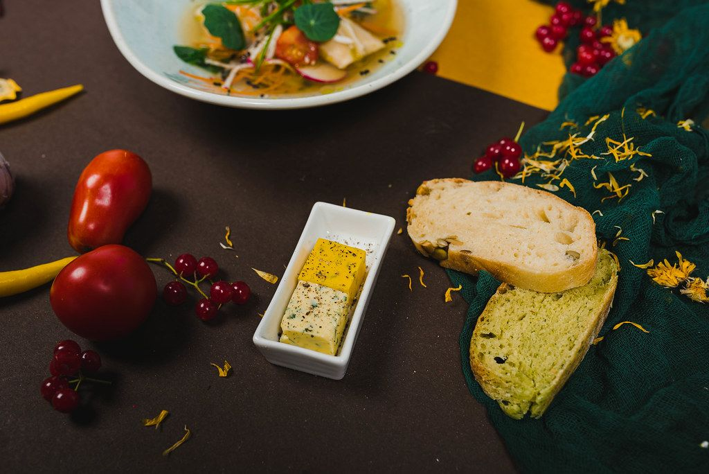 Käse, Brot und Gemüse auf dem schwarzen Tisch
