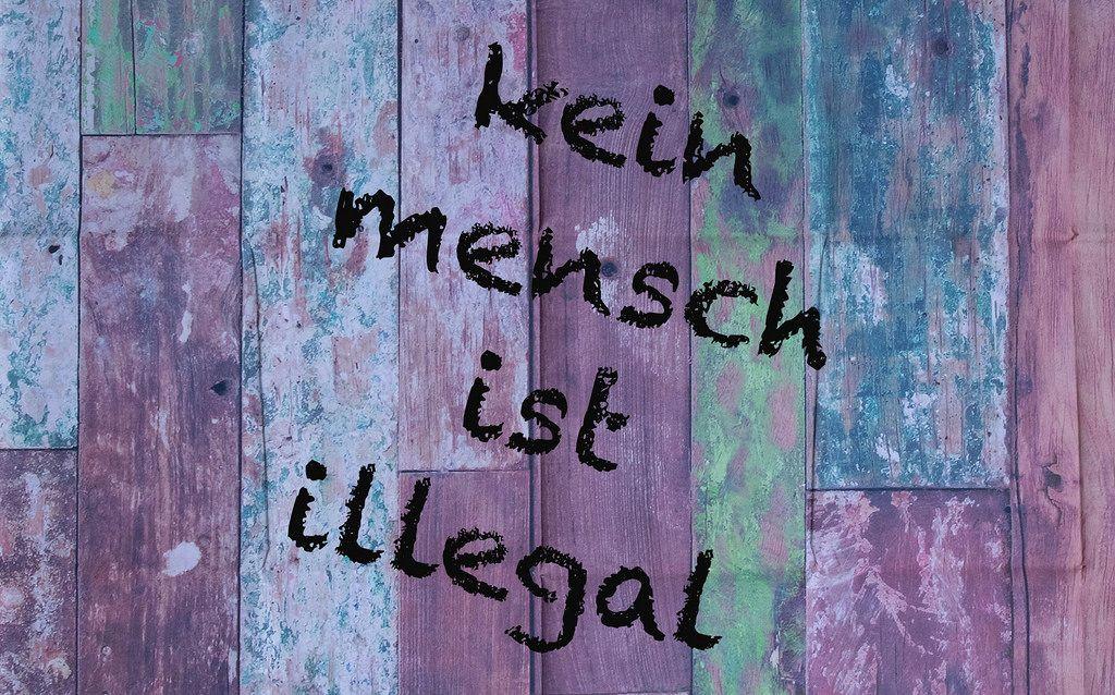 Kein Mensch ist illegal geschrieben auf einer heruntergekommenen Holzfassade