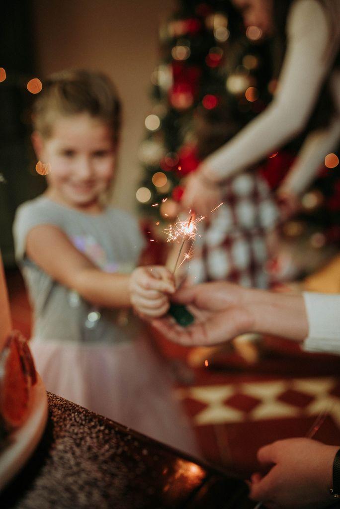 Kind überreicht Wunderkerze vor Tannenbaum und verbreitet festliche Stimmung