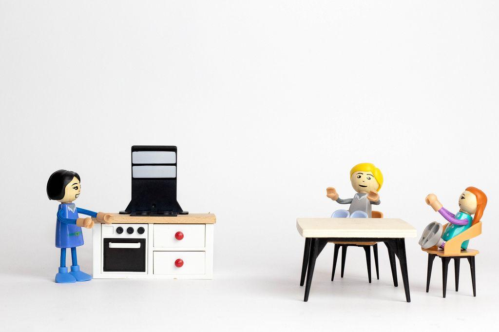 Kinder an einem Tisch warten auf das Abendessen mit der Mutter in der Küche - Modelfiguren