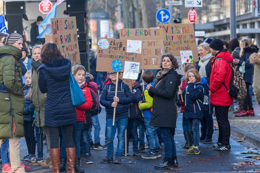Kinder mit Ihren Eltern nehmen am Klimastreik teil und halten Demoschilder in die Luft