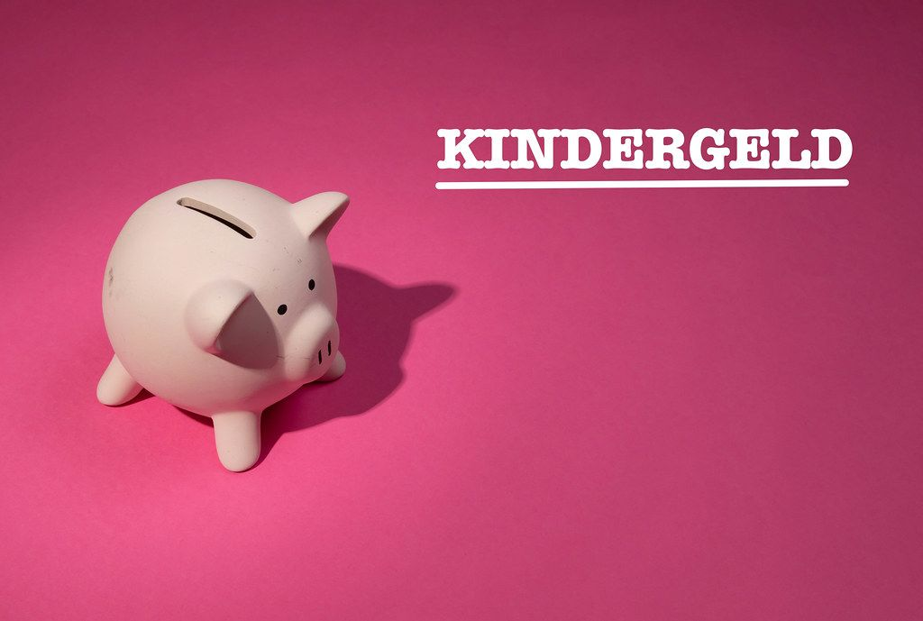 Kindergeld text with piggy bank on pink background