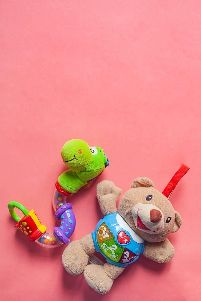 Kinderspielzeug Babyrassel und Plüschbär auf rosarotem Hintergrund mit Platz für eigenen Text