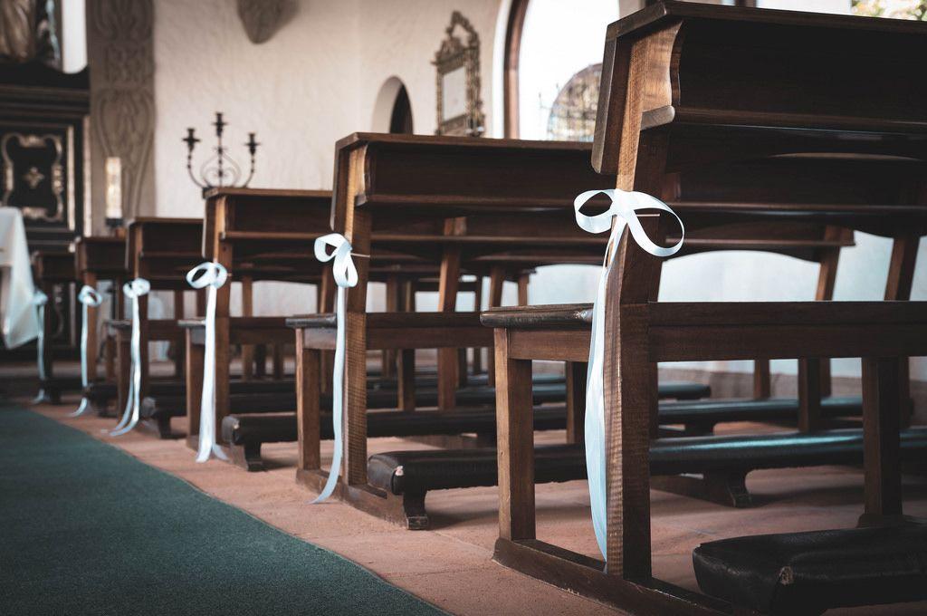 Kirchenbänke dekoriert mit weißen Schleifen