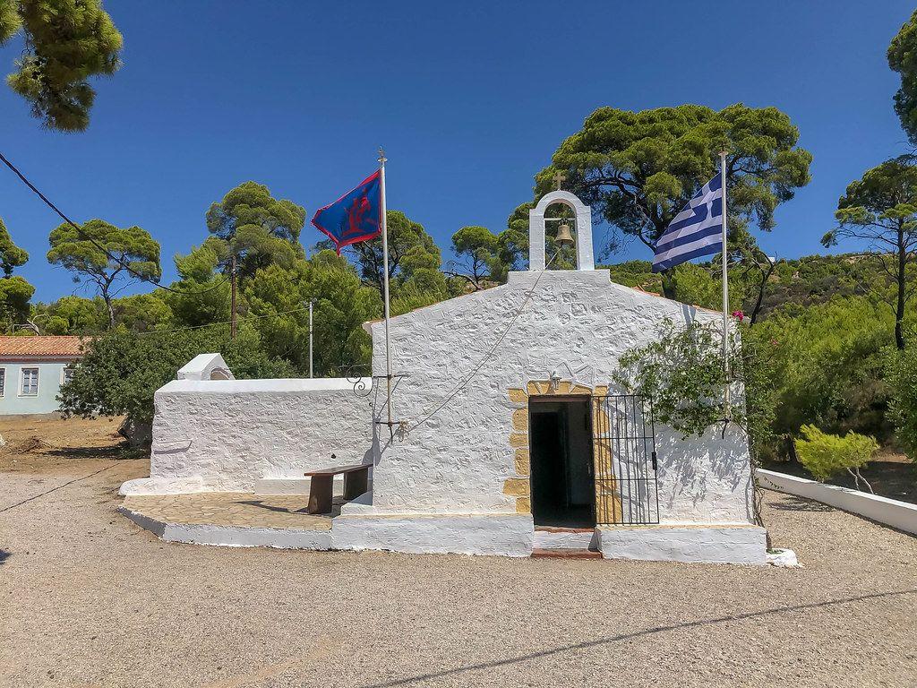 Kleine Kapelle mit Glocke, am Agii Anargiri Strand, mit wehenden Flaggen, auf der griechischen Insel Spetses