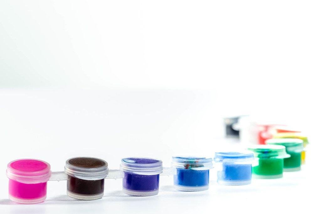 Kleine Pöttchen mit verschiedenen Farben zum Zeichnen vor weißem Hintergrund