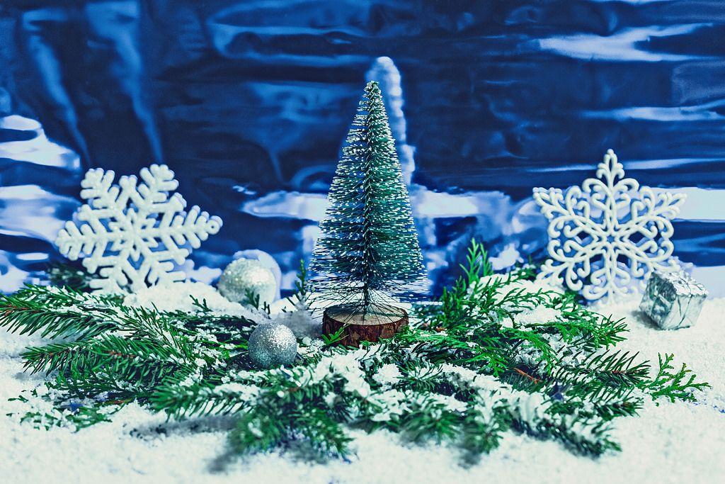 Kleiner Weihnachtsbaum zwischen beschneiten Tannenzweigen, Schneeflocken und Weihnachtsbaumkugeln