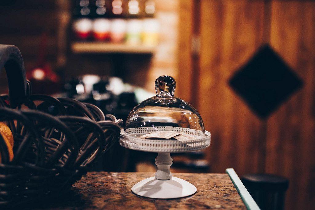 Kleines Servierbrett aus Glas mit Deckel vor unscharfem Hintergrund. Innenaufnahme im Cafe