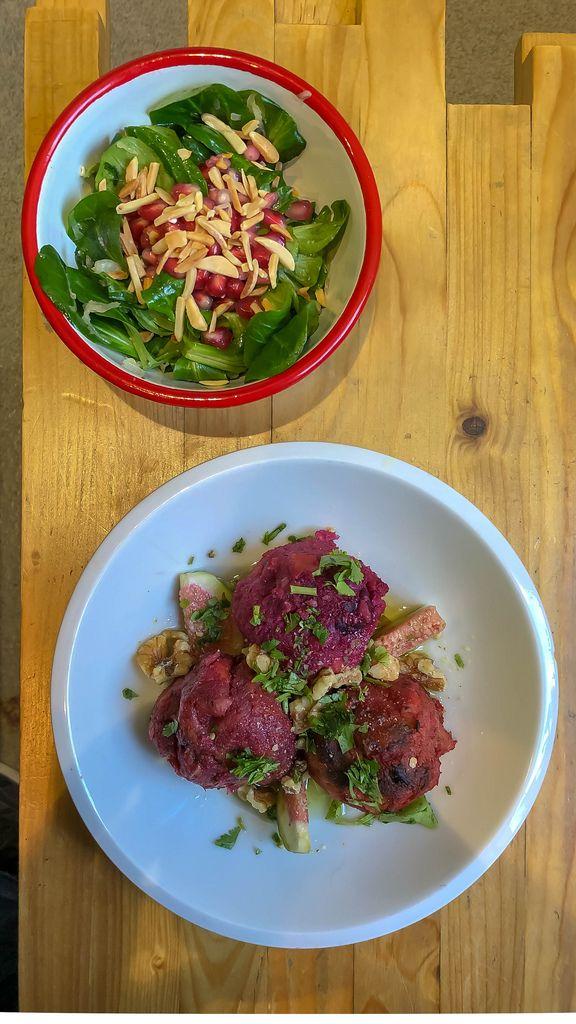 Knödel aus roter Bete mit Koriander, Feigen und Walnüssen und als Beilage Feldsalat mit Sauerkraut, garniert mit Mandeln und Granatapfel auf Holztisch