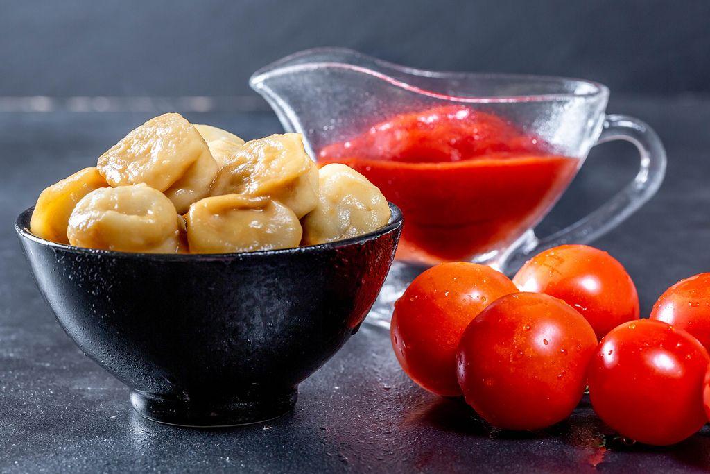 Knödeln in schwarzer Schale neben Sauciere mit Tomatensoße und frischen Tomaten auf schwarzem Tisch