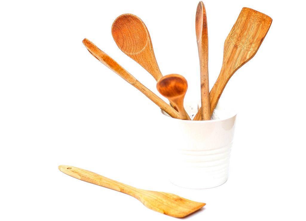 Kochutensilien aus Holz in weißer Schüssel vor weißem Hintergrund
