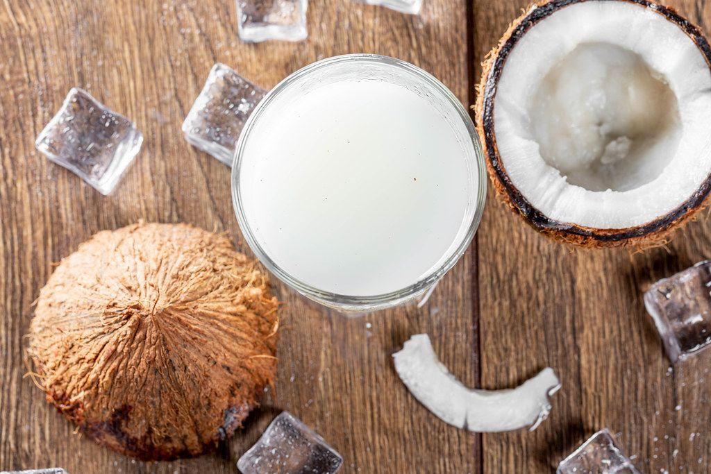 Kokosmilch im Glas, neben einer halbierten Kokosnuss und Eiswürfel, auf einem braunen Holztisch