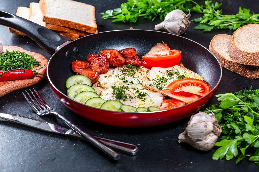 Konzeptbild zum Thema Frühstück, mit Spiegeleiern, frischem Gemüse und Würstchen, in einer Bratpfanne auf der Küchenarbeitsfläche