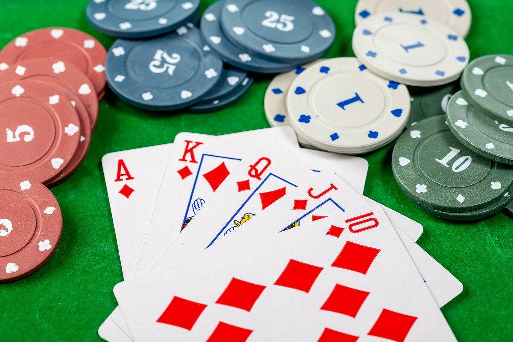 Konzeptbild zum Thema Glücksspiel mit Spielkarten, einem Royal Flush und Pokerchips auf einem grünen Spieltisch