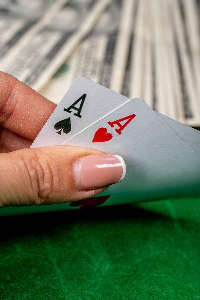 Konzeptbild zum Thema Glücksspiel um Geld, zeigt ein Pokerspiel mit Spielkarten in einer Frauenhand