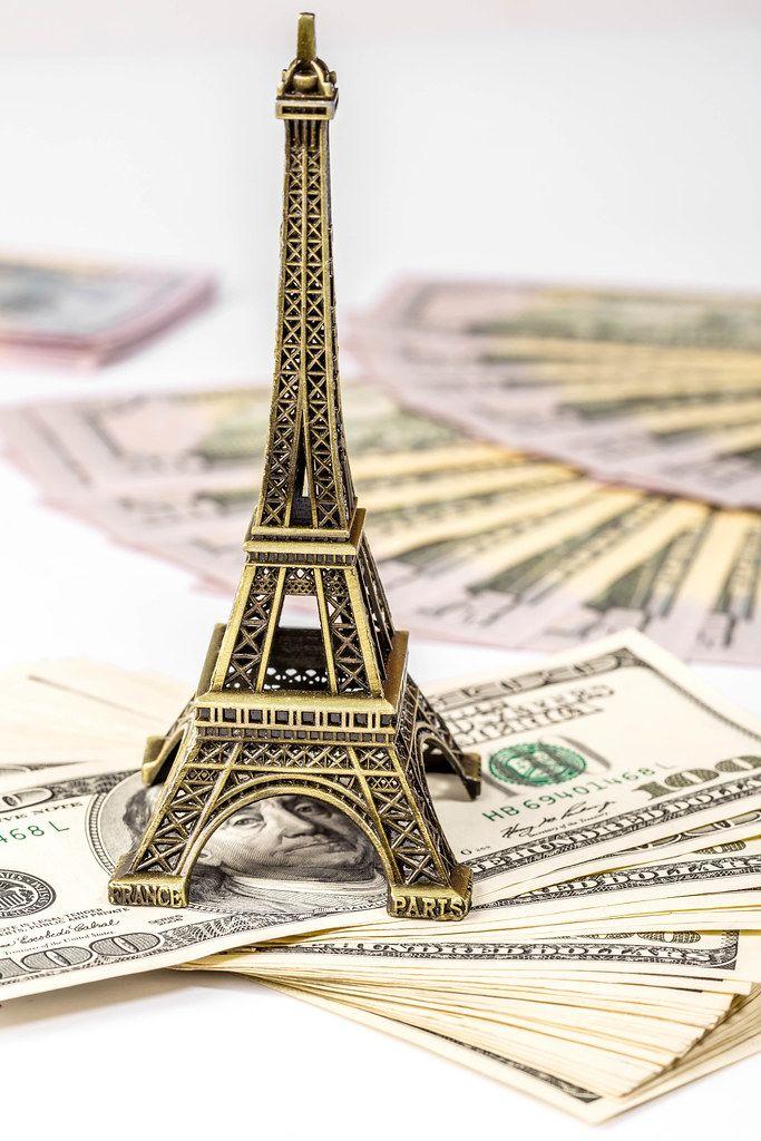 Konzeptbild zum Thema Reiseplanung zeigt einen Eiffelturm auf einem Geldstapel mit Dollarscheinen