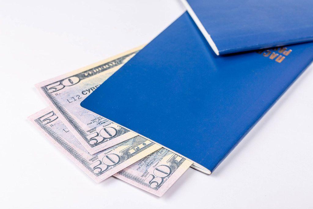 Konzeptbild zum Thema Verreisen mit zwei blauen Reisepässen und ausländischem Geldscheinen