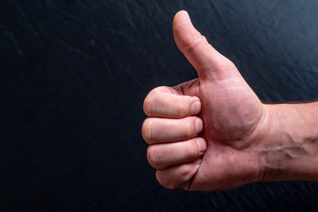Konzeptbild zur positiven Zustimmen zeigt eine Männerhand vor schwarzem Hintergrund mit dem Daumen nach oben, als ein